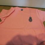ピング色に刺繍が入ったTシャツ